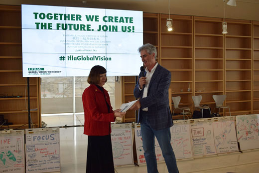 IFLA Secretary General Gerald Leitner hands IFLA President Donna Scheeder a draft summary report on the Global Vision Discussion