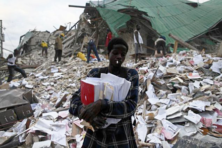 A man retrieving documents from the rubble